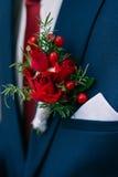 Fiore rosso nell'occhiello del suo sposo del rivestimento Mazzo di cerimonia nuziale Immagini Stock