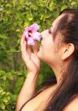 Fiore sentente l'odore della donna graziosa Immagine Stock Libera da Diritti