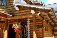 Fiori all'aperto dei vasi da fiori Sul portico Casa da una barra Contro i fiori della casa Immagine Stock