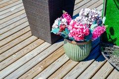 Fiori all'aperto dei vasi da fiori Sul portico Casa da una barra Contro i fiori della casa Fotografia Stock Libera da Diritti