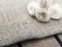 Fiori asciutti sulla tela di iuta della tela da imballaggio che licenzia sulla tavola di legno fotografia stock libera da diritti