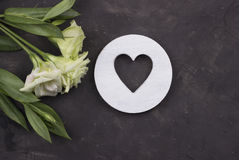 Fiori bianchi e cuore di legno su fondo concreto scuro Cartolina d'auguri Rosa rossa Immagini Stock Libere da Diritti