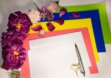 Fiori, busta e penna su un bianco Fotografia Stock