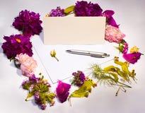 Fiori, busta e penna su un lillà Fotografia Stock
