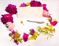 Fiori, busta e penna su un lillà Immagini Stock