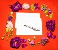 Fiori, busta e penna su un rosso Fotografia Stock Libera da Diritti