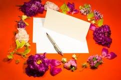 Fiori, busta e penna su un rosso Fotografie Stock