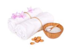 Elementi della stazione termale: fiori con gli asciugamani ed il sale isolati Fotografia Stock