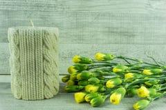 Fiori con i fiori gialli e una candela Fotografie Stock Libere da Diritti