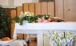 Fiori conservati in vaso nella chiesa sopra un altare santo Immagini Stock