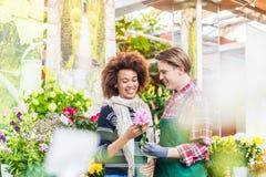 Fiori d'acquisto del cliente femminile allegro al consiglio di un venditore utile immagine stock