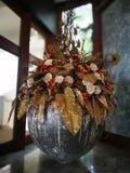 Fiori d'annata nella grande progettazione del vaso nel salone immagine stock