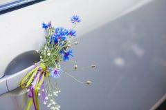 Fiori del campo sulla maniglia dell'automobile Immagine Stock