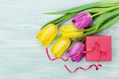 Fiori del contenitore e del tulipano di regalo sulla tavola rustica per il giorno dell'8 marzo, di Giornata internazionale della  Fotografie Stock Libere da Diritti