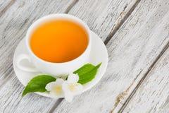 Fiori del gelsomino e tazza di tè verde su fondo di legno Immagine Stock