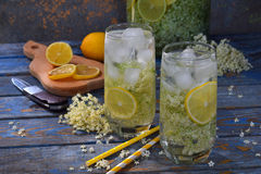 Fiori della bacca di sambuco e bevanda del limone Succo sano dell'anziano del rinfresco Vetro della limonata di sambuco sul bordo Immagine Stock