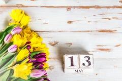 Fiori della primavera e blocchi di legno con la data di giorno delle madri, il 13 maggio, Immagini Stock