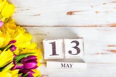 Fiori della primavera e blocchi di legno con la data di giorno delle madri, il 13 maggio, Immagine Stock Libera da Diritti