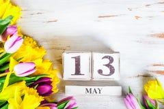 Fiori della primavera e blocchi di legno con la data di giorno delle madri, il 13 maggio, Fotografia Stock