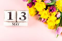 Fiori della primavera e blocchi di legno con la data di giorno delle madri, il 13 maggio, Immagine Stock