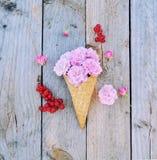 Fiori della rosa di rosa e ribes rosso maturo in cono gelato su fondo di legno rustico Fotografie Stock Libere da Diritti