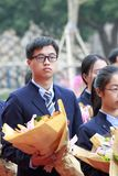 Fiori della tenuta dello studente maschio pronti a dedicare all'insegnante, adobe rgb Fotografia Stock