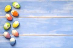 Fiori delle uova di Pasqua su fondo di legno blu Immagini Stock Libere da Diritti