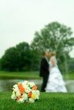 Fiori di cerimonia nuziale con baciare dello sposo e della sposa Immagini Stock Libere da Diritti