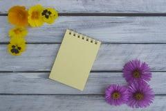 Fiori di estate e una nota su un fondo di legno leggero Immagini Stock Libere da Diritti