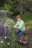 Fiori di raccolto della donna in giardino immagine stock libera da diritti