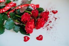 Fiori di Rosa, nastro rosso e cuori decorativi su fondo di legno leggero fotografia stock libera da diritti