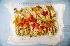 Fiori di zucca ripieni stuffed courgette flowers, Italy. Stuffed courgette flowers with ricotta cheese, baked in oven with tomatoes and presented over cook paper royalty free stock photography