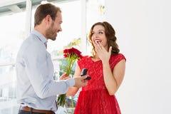 Fiori e anello di fidanzamento d'offerta dell'uomo Fotografia Stock