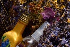 Fiori e bottiglie con olio aromatico Fotografia Stock