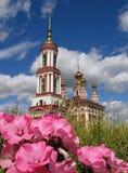 Fiori e chiesa russa. fotografia stock