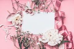 Fiori e disposizione del petalo intorno a carta in bianco su fondo rosa con i nastri, vista superiore Lettera di sensibilità di a immagini stock