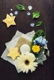 Fiori e foglie tropicali con la candela e le stelle d'oro Fotografia Stock