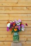 Fiori e parete di legno Immagini Stock