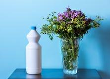 Fiori e prodotto per la pulizia bianco in vaso immagine stock libera da diritti