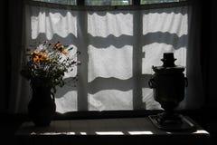 Fiori e samovar su un davanzale della finestra Immagini Stock