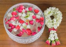 Fiori ed acqua di ghirlanda tailandesi con il gelsomino e la corolla delle rose dentro fotografia stock libera da diritti