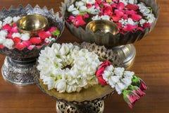 Fiori ed acqua di ghirlanda tailandesi con il gelsomino e la corolla delle rose dentro immagine stock