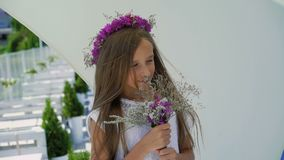 Fiori felici di fiuto della ragazza in mani e sorridere alla barra di baia lentamente stock footage