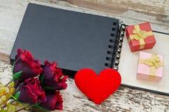 Fiori, forma del cuore e due contenitori di regalo sul libro aperto Fotografia Stock