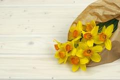 Fiori gialli del narciso del mazzo in carta sulla tavola immagine stock
