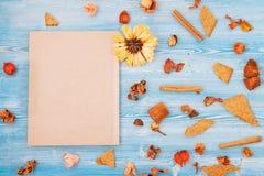 Fiori gialli e rossi su una struttura di legno blu del blocco note e del fondo, concetto del contesto per un posto della cartolin immagine stock