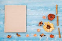 Fiori gialli e rossi su una struttura di legno blu del blocco note e del fondo, concetto del contesto per un posto della cartolin fotografie stock