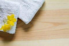 Fiori gialli sugli asciugamani bianchi con ombra molle su fondo di legno d'annata Fotografia Stock