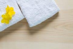 Fiori gialli sugli asciugamani bianchi con ombra molle su fondo di legno d'annata Fotografie Stock Libere da Diritti