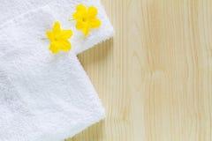 Fiori gialli sugli asciugamani bianchi con ombra molle su fondo di legno d'annata Fotografie Stock